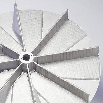Wear-protected impeller for a material transport fan